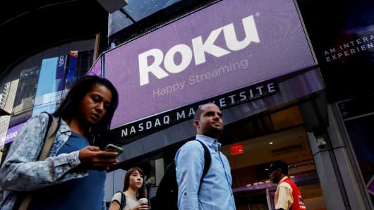 People pass by a video sign display with the logo for Roku Inc, a Fox-backed video streaming firm, that held it's IPO at the Nasdaq Marketsite in New York, U.S., September 28, 2017.