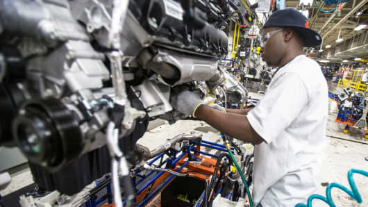 A worker installs parts on the engine of a Chrysler SUV as it moves along the assembly line at the Jefferson North Assembly Plant in Detroit Michigan.