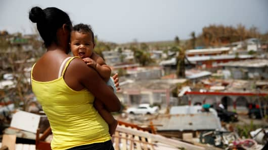 Ysamar Figueroa carrying her son Saniel, looks at the damage in the neighborhood after the area was hit by Hurricane Maria, in Canovanas, Puerto Rico September 26, 2017.
