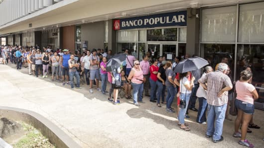 People stand in line to withdraw cash from an automatic teller machine (ATM) after Hurricane Maria heavily damaged the government-run electricity system in the Miramar neighborhood of San Juan, Puerto Rico, on Tuesday, Sept. 26, 2017.