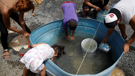 People fill containers with water at an area hit by Hurricane Maria in Canovanas, Puerto Rico, September 26, 2017. Picture taken on September 26, 2017.