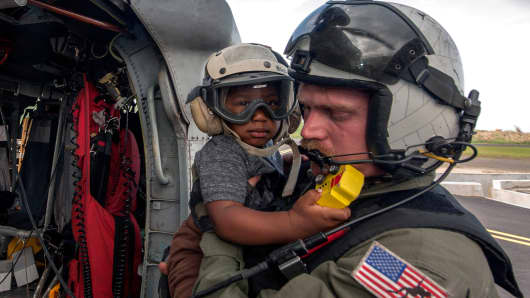 U.S. Navy aircrewman carries an evacuee off an MH-60S Sea Hawk helicopter in the Caribbean region as part of Defense of Department support for those affected by Hurricane Maria.