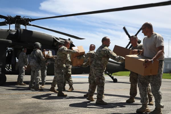 Puerto Rican National Guardsmen load a helicopter with food and water to bring to hurricane survivors.