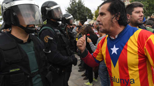 A man dressed in the Catalonian flag confronts officers as police move in on the crowds as members of the public gather outside to prevent them from stopping the opening and intended voting in the referendum at a polling station where the Catalonia President Carles Puigdemont will vote later today on October 1, 2017 in Sant Julia de Ramis, Spain.