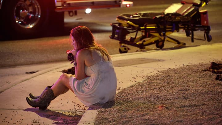 A woman sits on a curb at the scene of a shooting outside of a music festival along the Las Vegas Strip, Monday, Oct. 2, 2017, in Las Vegas. Multiple victims were being transported to hospitals after a shooting late Sunday at a music festival on the Las Vegas Strip.