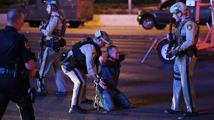 Police officers stop a man who drove down Tropicana Ave. near Las Vegas Boulevard and Tropicana Ave, which had been closed after a mass shooting at a country music festival that left at least 2 people dead nearby on October 2, 2017 in Las Vegas, Nevada. The man was released.