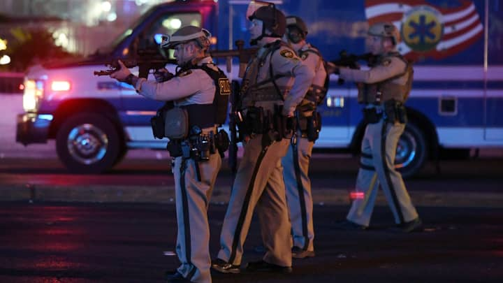Police officers point their weapons at a car driving down closed Tropicana Ave. near Las Vegas Boulevard after a reported mass shooting at a country music festival nearby on October 2, 2017 in Las Vegas, Nevada.