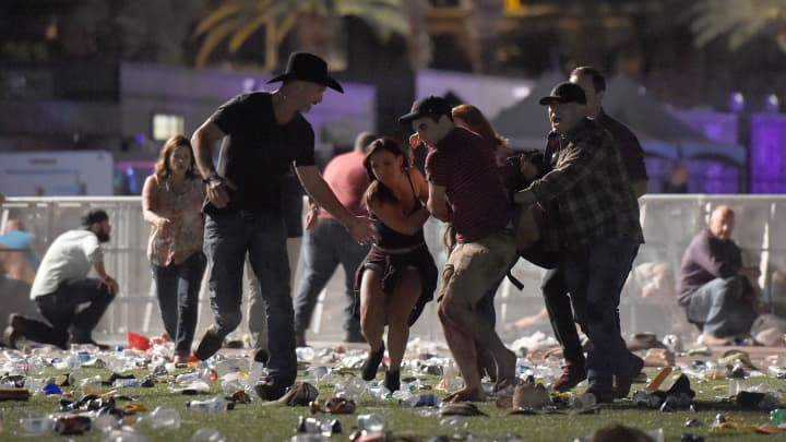 People carry a peson at the Route 91 Harvest country music festival after apparent gun fire was heard on October 1, 2017 in Las Vegas, Nevada.