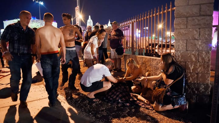 People tend to the wounded outside the Route 91 Harvest Country music festival grounds after an apparent shooting on October 1, 2017 in Las Vegas, Nevada.