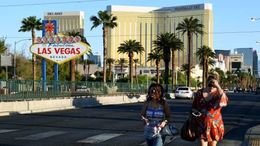 Two festival-goers leave the area around the Mandalay Hotel after a gunman killed more than 50 people and wounded more than 500 others when he opened fire on a country music concert in Las Vegas, Nevada on October 2, 2017.