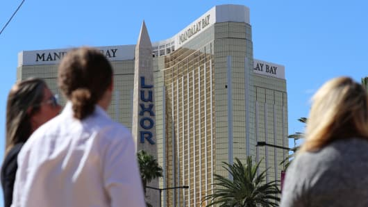 People stand behind police barrier tape outside the Luxor hotel Obelisk and the Mandalay Bay Resort and Casino, following a mass shooting at the Route 91 Festival in Las Vegas, Nevada, October 2, 2017.