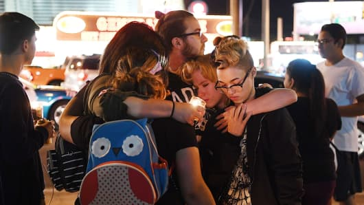 People embrace during a vigil on the Las Vegas strip for the victims of the Route 91 Harvest country music festival shootings on October 2, 2017, in Las Vegas.