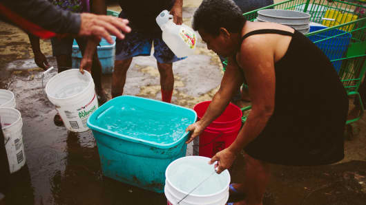 People buckets filled with water after Hurricane Maria in Corozal, Puerto Rico, on Saturday, Sept. 30, 2017.