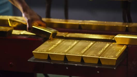 A worker lifts a gold bullion bar from a conveyor machine at the Rand Refinery plant in Germiston, South Africa, on Aug. 16. 2017.
