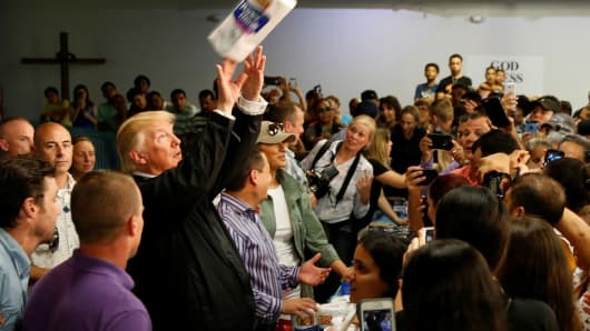 President Donald Trump tosses rolls of paper towels to people at a hurricane relief distribution center at Calvary Chapel in San Juan Puerto Rico
