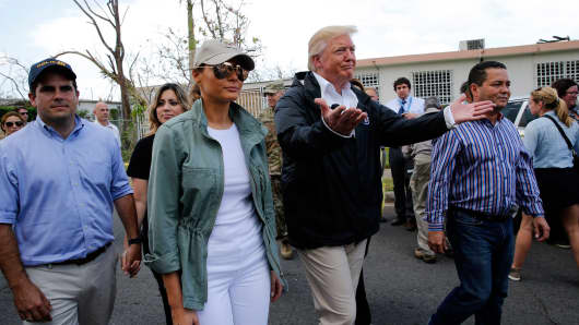 President Donald Trump and first lady Melania Trump walk through a neighborhood damaged by Hurricane Maria in Guaynabo, Puerto Rico, U.S., October 3, 2017.