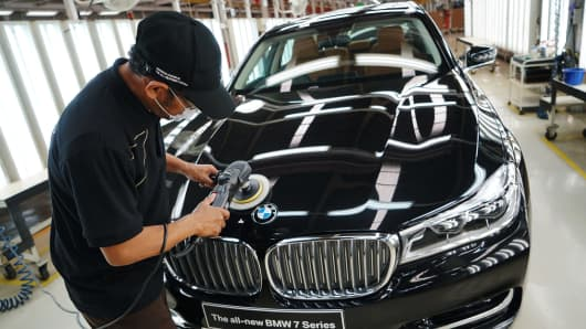An employee polishes the hood of a BMW AG 7-Series sedan at the assembly line.