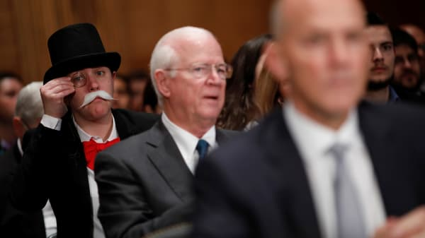 A hearing attendee dressed as Monopoly's Uncle Pennybags looks on as Richard Smith, former chairman and CEO of Equifax, Inc., testifies before the U.S. Senate Banking Committee on Capitol Hill in Washington, U.S., October 4, 2017.