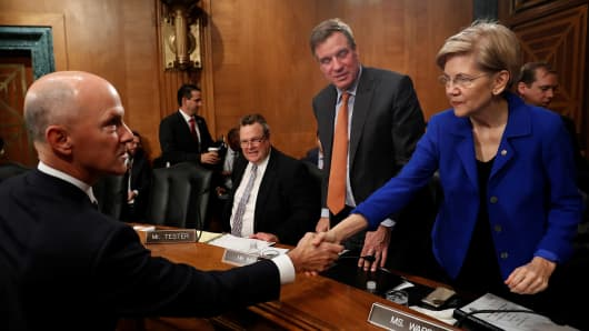 Richard Smith, former chairman and CEO of Equifax, Inc., greets Sen. Elizabeth Warren (D-MA) prior to testifying before the U.S. Senate Banking Committee on Capitol Hill in Washington, U.S., October 4, 2017.