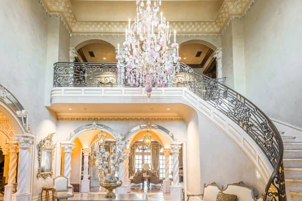 The pink and white glass chandelier and marble columns are elaborate features of this 16,000 square foot home.