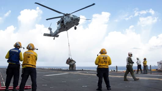 Sailors aboard the amphibious assault ship USS Kearsarge (LHD 3) observe as an MH-60 Sea Hawk helicopter drops pallets of supplies onto the flight deck during a replenishment-at-sea with the fast combat support ship USNS Supply (T-AOE 6) for relief efforts in the aftermath of Hurricane Maria in Puerto Rico on September 28, 2017.