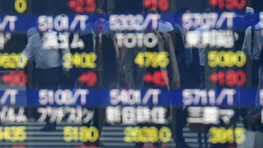 Pedestrians are reflected in the window of a securities company showing stock prices on the Tokyo Stock Exchange in Tokyo on October 3, 2017.