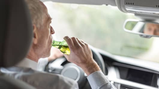 Man drinking alcohol while driving a car.