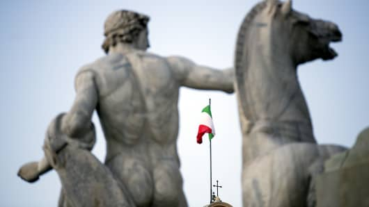 The Italian national flag, seen between statues, flies atop the Quirinale palace, the office of Italy's president in Rome, Italy.