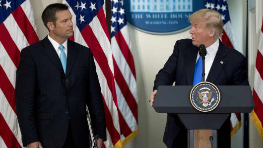 President Donald Trump speaks as Kris Kobach, Kansass secretary of state, left, listens during the initial meeting of the Presidential Advisory Commission on Election Integrity at the Eisenhower Executive Office Building in Washington, D.C., U.S., on Wednesday, July 19, 2017.
