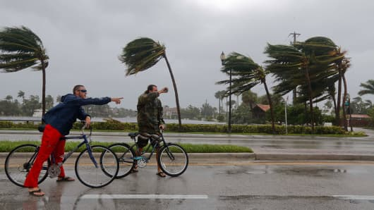 Clay Pace (L) and William Williams (R) take a break from this bicycle ride near downtown Ft. Lauderdale FL September 10, 2017 as Hurricane Irma's wind and rain take effect.