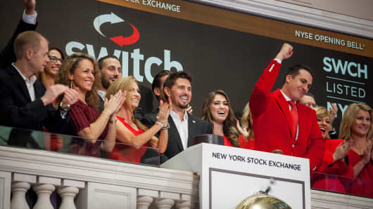 Rob Roy, founder and chief executive officer of Switch Inc., center, rings the opening bell before the company's initial public offering (IPO) on the floor of the New York Stock Exchange (NYSE) in New York, U.S., on Friday, Oct. 6, 2017.