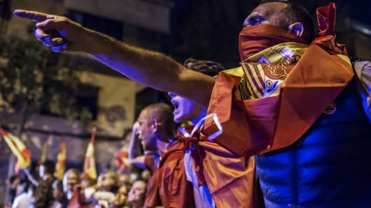 An anti-separatist demonstrator in support of the Spanish National Police and Civil Guard gestures while wearing a Spanish national flag during a protest near a Civil Guard barrack in Sant Boi de Llobregat, Spain, on Thursday, Oct. 5, 2017. Spanish Prime MinisterMariano Rajoyconvenes his cabinet on Friday as the financial and politic