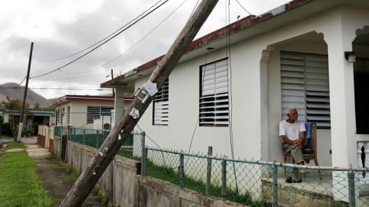 A resident sits on his porch underneath a damaged power line as recovery efforts continue following Hurricane Maria in Ceiba, Puerto Rico, October 4, 2017.