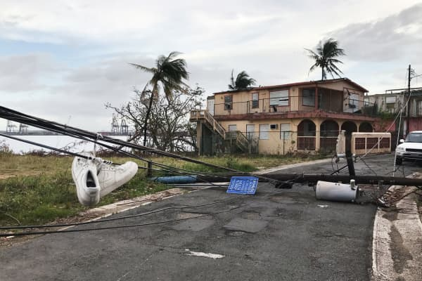Sneakers hang from downed wires in the wake of Hurricane Maria in the Vietnam section of Guaynabo, Puerto Rico on October 1, 2017.