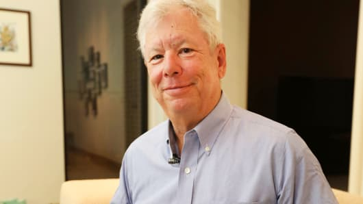 In this photo provided by the University of Chicago, Richard Thaler poses for a photo with his books at his home in Chicago after winning the Nobel prize in economics, Monday, Oct. 9, 2017.