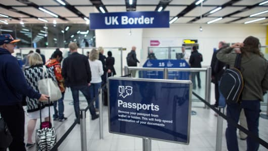 Border Force check the passports of passengers arriving at Gatwick Airport in London.