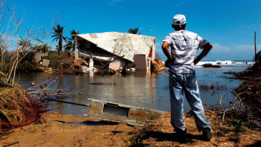 A man surveys a house that was washed away by heavy surf during the passing of Hurricane Maria in Manati, Puerto Rico on October 6, 2017.