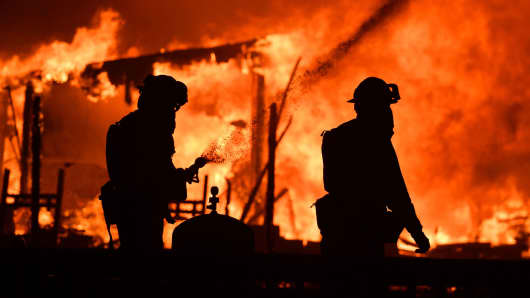 Firefighters douse flames as a home burns in the Napa wine region in California on October 9, 2017, as multiple wind-driven fires continue to whip through the region.