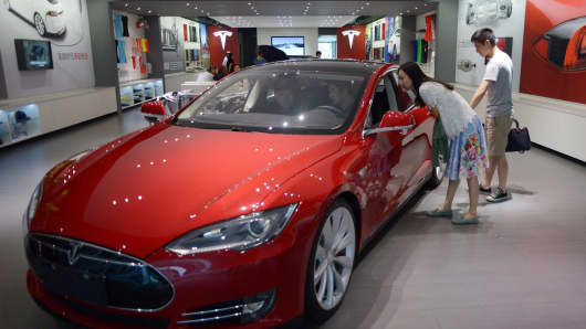 People look at a Model S sedan displayed in the Tesla showroom at Parkview Green Shopping Mall in Beijing, China. Electric-car maker Tesla opened its first store in Beijing in 2013.