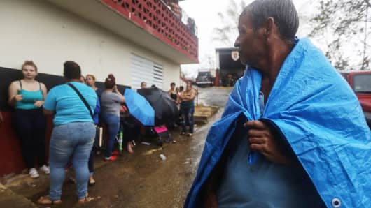 Arian Rodriguez covers himself with a tarp as residents wait in the rain to register with FEMA more than two weeks after Hurricane Maria hit the island, on October 9, 2017 in Jayuya, Puerto Rico.
