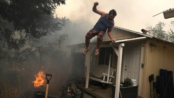 A resident rushes to save his home as an out of control wildfire moves through the area on October 9, 2017 in Glen Ellen, California.