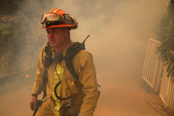 A Los Angeles County firefighter monitors approching flames near a building as an out of control wildfire moves through the area on October 9, 2017 in Yountville, California.
