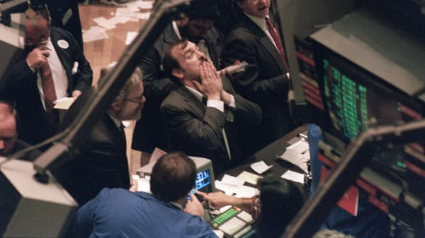 A trader (c) on the New York Stock Exchange looks at stock rates 19 October 1987 as stocks were devastated during one of the most frantic days in the exchange's history. The Dow Jones index plummeted over 200 points in record trading.