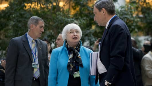 Janet Yellen, chair of the U.S. Federal Reserve, center, talks to Mario Draghi, president of the European Central Bank (ECB), before the IMF governors' group photo at the International Monetary Fund (IMF) and World Bank Group Spring Meetings in Washington, D.C. (File photo).