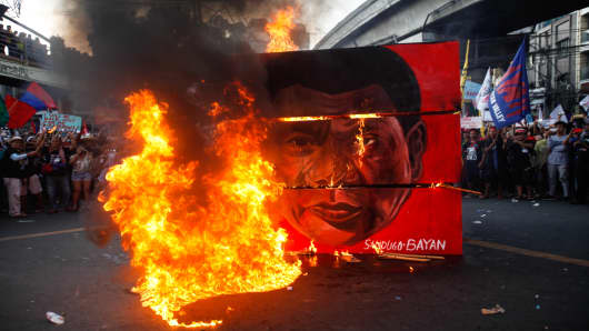 A cubic effigy painted with the face of President Duterte is set on fire by activists during a rally commemorating the 45th anniversary of the declaration of martial law in Manila on Sept 21 2017.