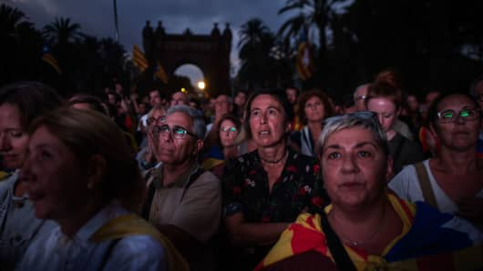Pro-independence supporters react as they watch a big screen and wait for the address of Catalan President Carles Puigdemont outside the Parliament of Catalunyaon October 10, 2017 in Barcelona, Spain.