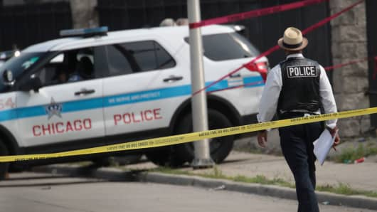 Police investigate the murder of a young man found shot to death in the back seat of a bullet-riddled car on June 30, 2017 in Chicago, Illinois.