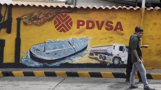 Pedestrians walk past a Petroleos de Venezuela SA (PDVSA) mural in Caracas, Venezuela.