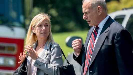 White House Chief of Staff John Kelly and Deputy Chief of Staff Kirstjen Nielsen speak together as they walk across the South Lawn of the White House in Washington, Aug. 22, 2017.