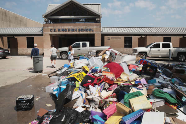 Volunteers and students from C.E. King High School help to clean up the school after torrential rains caused widespread flooding in the area during Hurricane and Tropical Storm Harvey